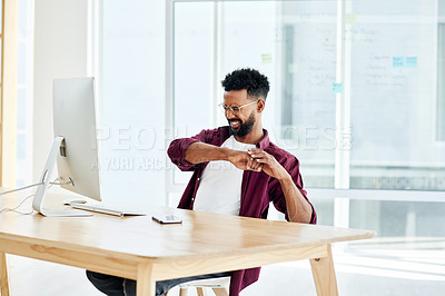 Buy stock photo Cropped shot of a businessman looking uncomfortable while sitting at his desk