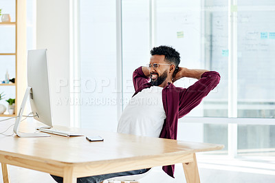 Buy stock photo Shot of a man frowning while stretching at his desk