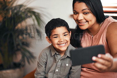 Buy stock photo Shot of a mother and her little son taking selfies together at home