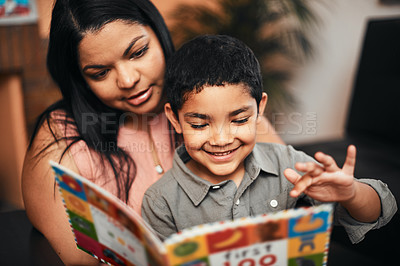 Buy stock photo Shot of a mother and her little son reading a book together at home
