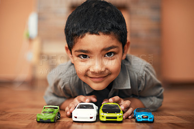 Buy stock photo Portrait of an adorable little boy playing with toy cars at home