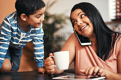 Buy stock photo Shot of a mother talking on a cellphone while using a digital tablet with her son alongside her at home