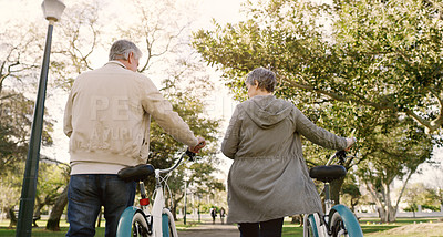 Buy stock photo Rearview shot of a senior couple going for a bicycle ride in the park