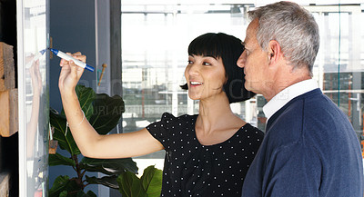 Buy stock photo Shot of two businesspeople brainstorming with notes on a whiteboard in an office