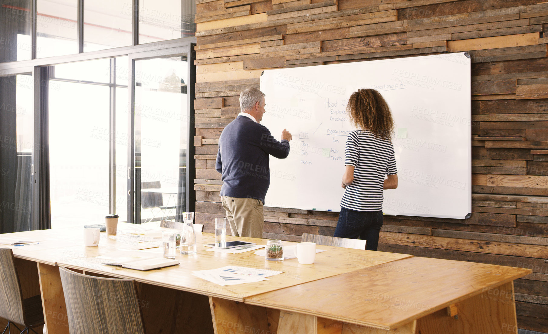 Buy stock photo Rearview shot of two businesspeople brainstorming with notes on a whiteboard in an office