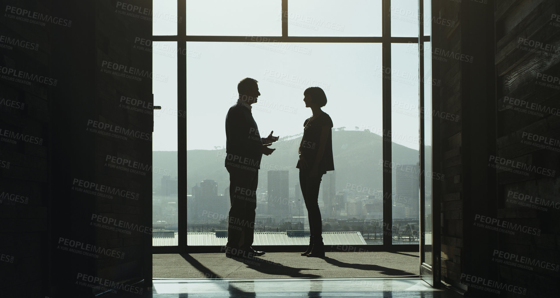 Buy stock photo Shot of two businesspeople having a discussion while standing at a window in an office