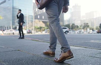Buy stock photo Shot of an unrecognizable businessman walking through the city