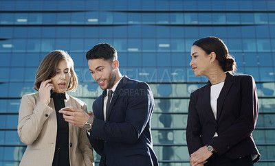 Buy stock photo Shot of a young businessman sharing good news on his smartphone with two businesswomen against an urban background