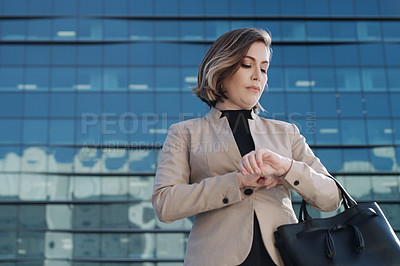 Buy stock photo Shot of a businesswoman checking the time on her watch while waiting against an urban background