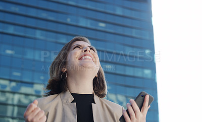 Buy stock photo Shot of a young businesswoman using a smartphone and celebrating good news against an urban background