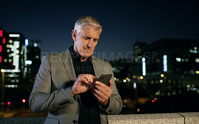 Buy stock photo Shot of a mature businessman using a smartphone in the city at night