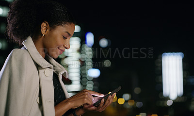 Buy stock photo Shot of a young businesswoman using a smartphone in the city at night