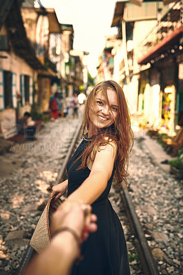 Buy stock photo Shot of a woman pulling her partner by the hand while exploring a foreign city