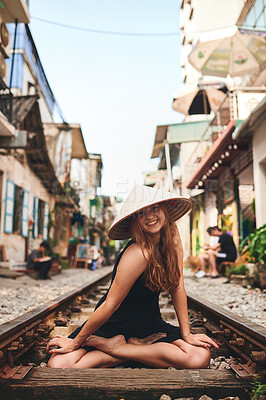Buy stock photo Shot of a woman wearing a conical hat while sitting on a railway track