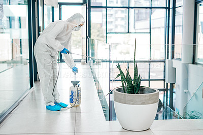Buy stock photo Shot of a young woman wearing a hazmat suit while using a chemical sprayer to sanitise a building