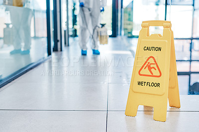 Buy stock photo Closeup shot of a wet floor sign in a building being sanitised