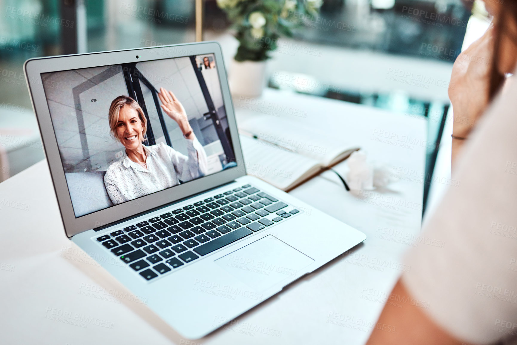 Buy stock photo Shot of a mature woman waving while appearing on a laptop screen during a video call