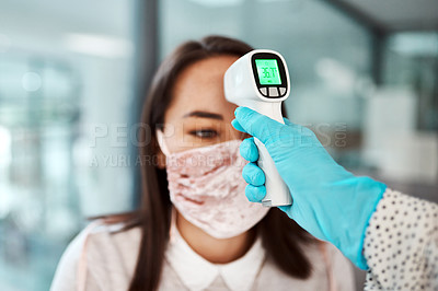 Buy stock photo Shot of a young businesswoman getting her temperature taken with an infrared thermometer in an office