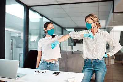 Buy stock photo Shot of two businesswomen bumping elbows in an office