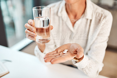Buy stock photo Closeup shot of an unrecognisable businesswoman holding a glass of water and medication in an office