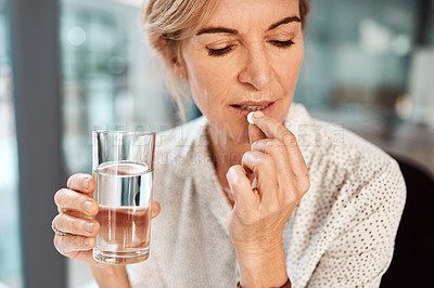 Buy stock photo Shot of a mature businesswoman taking medication in an office