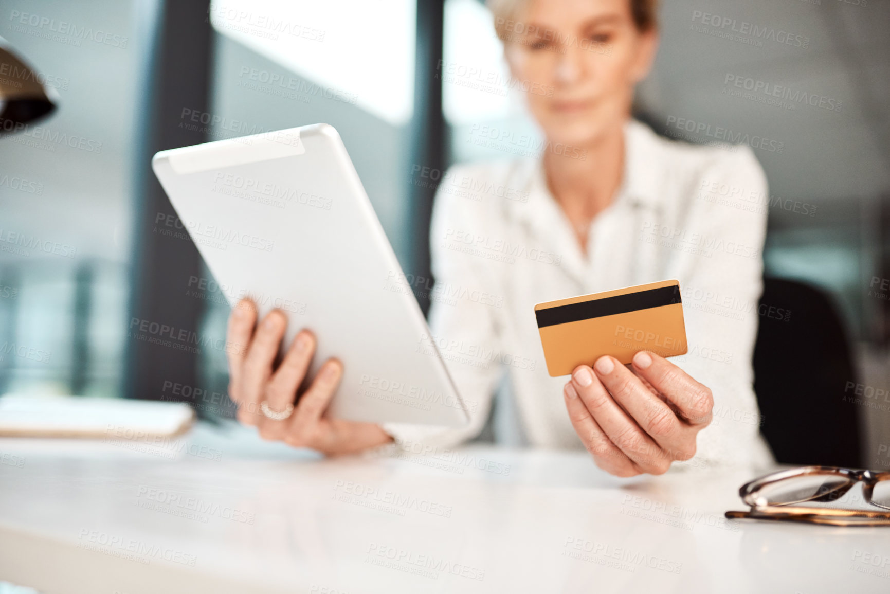 Buy stock photo Closeup shot of an unrecognisable businesswoman using a digital tablet and credit card in an office