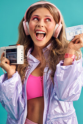 Buy stock photo Studio shot of a young woman holding a cassette player while dressed in 80s clothing