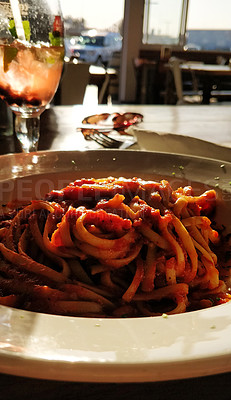 Buy stock photo Shot of a freshly prepared plate of pasta with a tomato based sauce on a plate in a restaurant