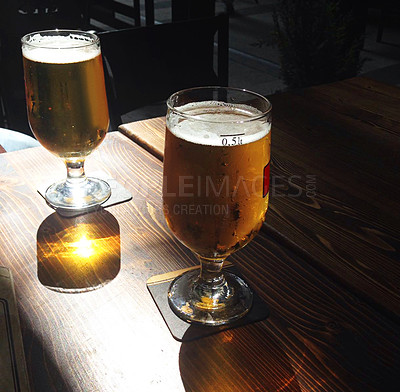 Buy stock photo Shot of two glasses filled with beer on a table at a restaurant in Istanbul