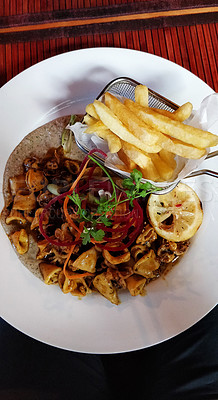 Buy stock photo Shot of freshly made seafood served with french fries on a plate in a restaurant