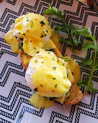 Buy stock photo Shot of eggs benedict served with hollandaise sauce on a slice of toasted bread