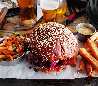 Buy stock photo Shot of a burger served with french fries and beer on a table at a restaurant