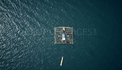 Buy stock photo High angle shot of a built fishing structure floating in the middle of the ocean called a kelong
