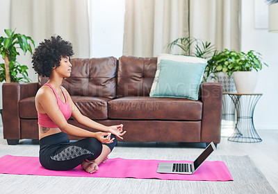 Buy stock photo Shot of a beautiful young woman using her laptop while practising yoga at home