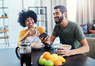 Buy stock photo Shot of a young couple looking at something on a cellphone while having breakfast at home