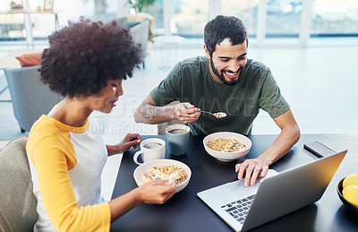 Buy stock photo Shot of a young couple using a laptop while having breakfast at home