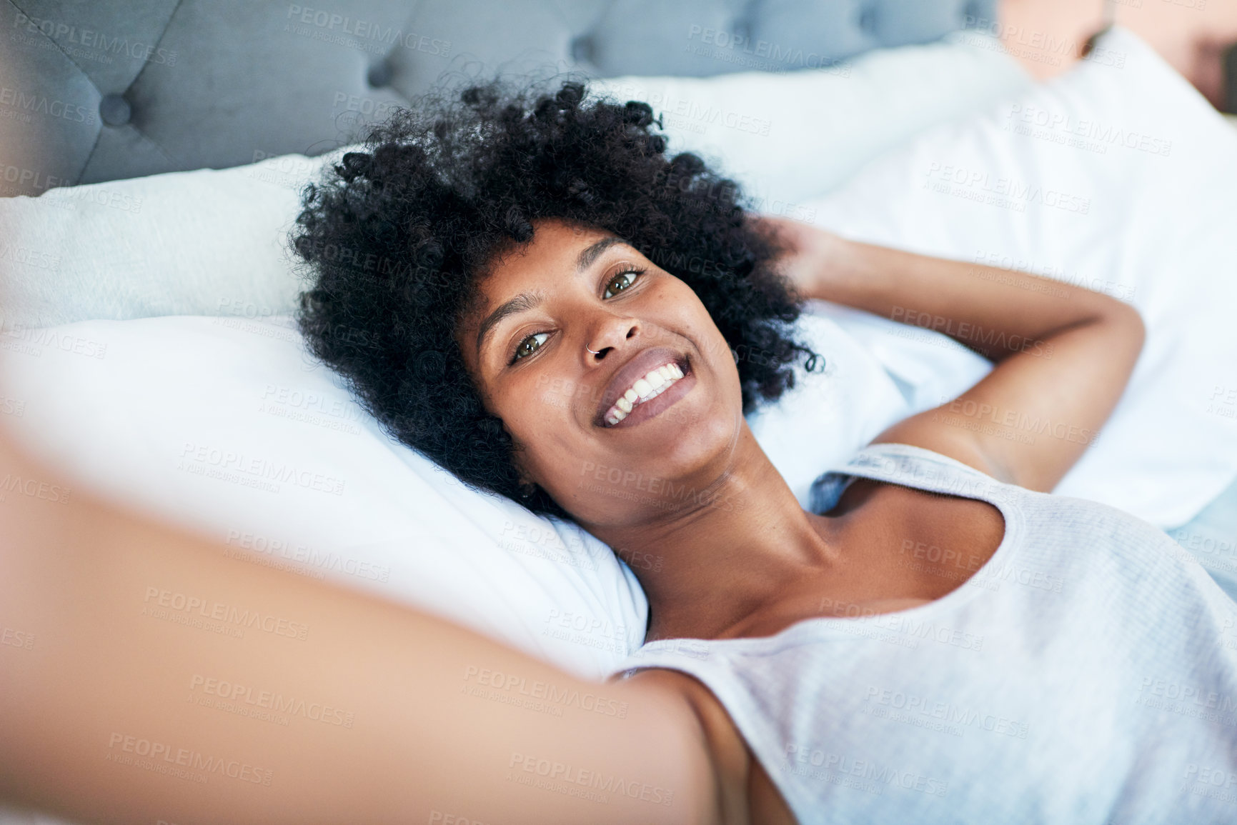 Buy stock photo Cropped shot of a young woman taking a selfie while lying in bed