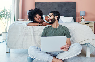 Buy stock photo Shot of a man using his laptop while sitting in the bedroom with his girlfriend