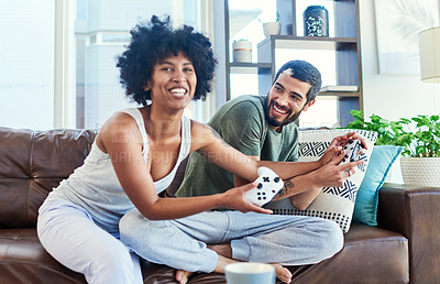 Buy stock photo Shot of a young couple having fun while playing video games at home
