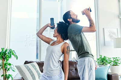 Buy stock photo Cropped shot of a couple having a sing along at home