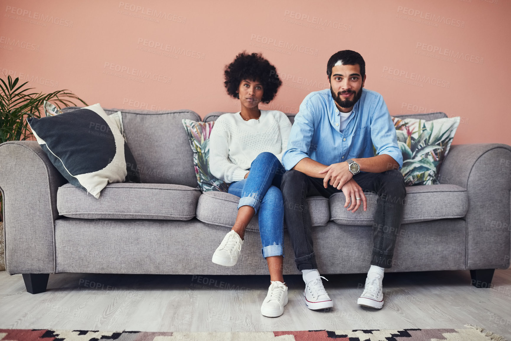 Buy stock photo Portrait of a young couple sitting on the sofa at home