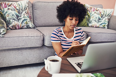 Buy stock photo Shot of a young woman making notes while using her laptop at home
