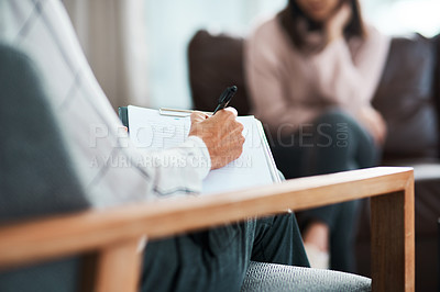 Buy stock photo Cropped shot of a psychologist writing notes during a therapeutic session with her patient