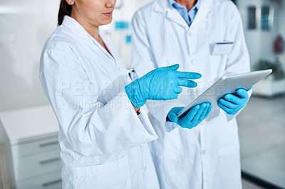 Buy stock photo Closeup shot of two scientists working together on a digital tablet in a lab