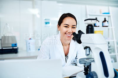Buy stock photo Portrait of a young scientist using a microscope in a lab