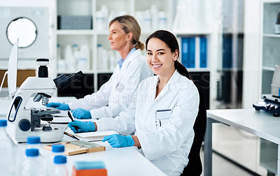 Buy stock photo Portrait of a young scientist working in a lab with her colleague in the background