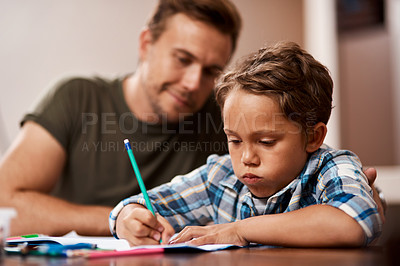 Buy stock photo Shot of a man sitting with his son while he does his homework