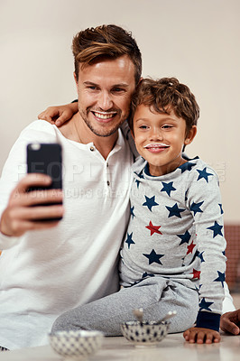 Buy stock photo Cropped shot of a young boy and his dad taking a selfie while having breakfast at home
