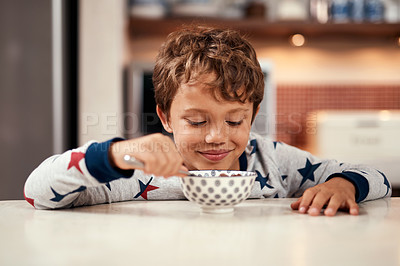 Buy stock photo Cropped shot of a young boy eating cereal at home