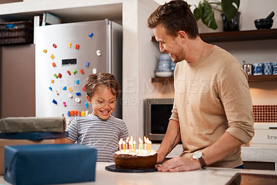 Buy stock photo Shot of a young boy looking happy while celebrating his birthday with his dad